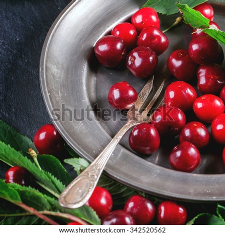 Vintage plate of fresh cherries with leaves, served with dessert fork over black. Square image with selective focus - stock photo