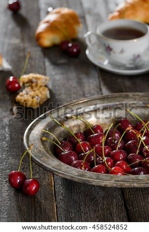 Vintage plate with cherries. Vertical shot of tasty food. A cup of hot tea and fresh croissants in the background. - stock photo