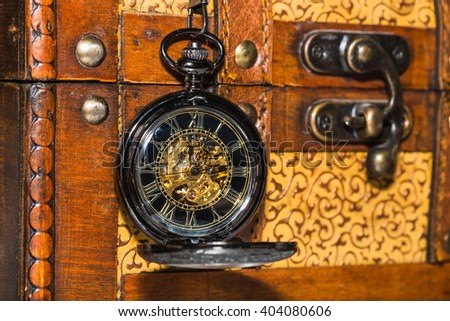 vintage pocket watch against the background of an old trunk - stock photo