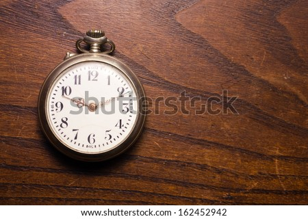 Vintage pocket-watch in the rustic desk - stock photo
