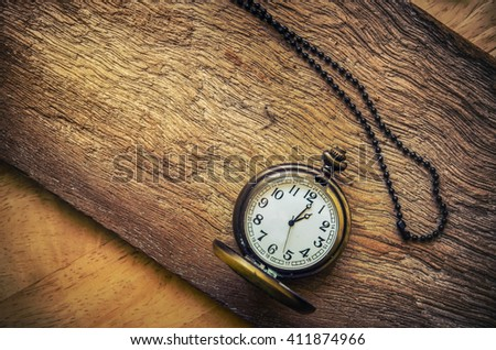 vintage pocket watch on wood board background - stock photo
