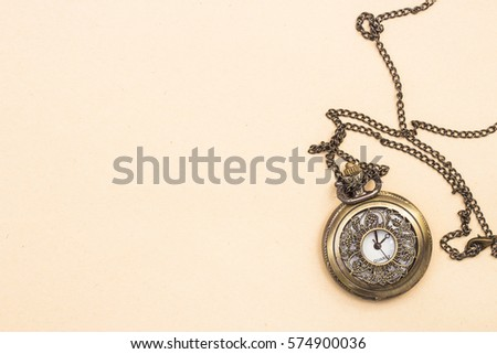 Vintage pocket watch with a chain on a background of the old paper