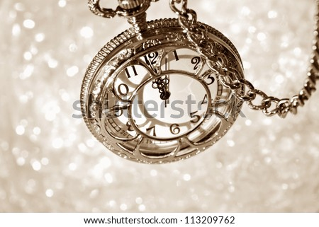 Vintage pocket watch with chain as viewed from above over bokeh background.  Side lighting with shadows for effect. Sepia toned macro with shallow dof.  Selective focus on the number 12. - stock photo