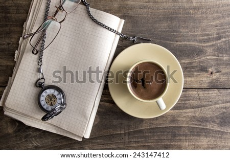 Vintage pocket watch with cup of coffee on old book closeup - stock photo