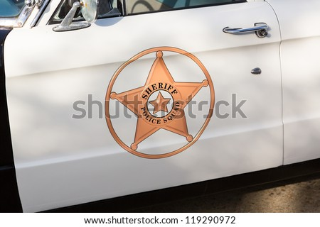 Vintage police car with detail focus on door and reflections of warning lights in paint - stock photo