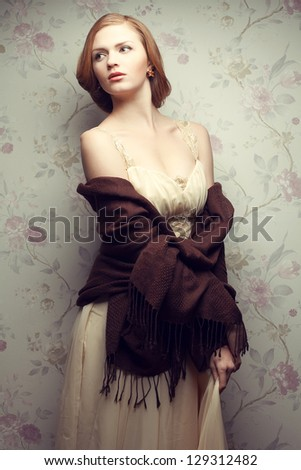 Vintage portrait of a glamorous red-haired (ginger) girl posing in great beige dress. Studio shot - stock photo