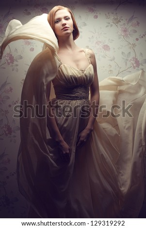 Vintage portrait of a happy glamorous red-haired (ginger) girl posing in great flying beige dress. Studio shot - stock photo