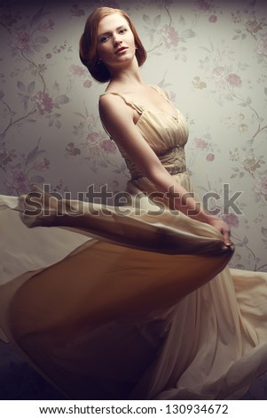 Vintage portrait of a happy glamorous red-haired (ginger) girl posing in great flying beige dress and dancing. Retro style. Studio shot - stock photo