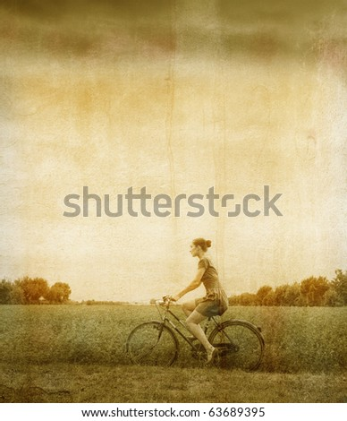 Vintage portrait of a woman riding a bike in the country - stock photo