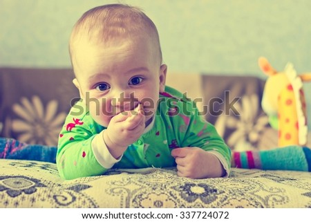 Vintage portrait of adorable serious baby boy eating cabbage - stock photo