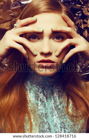 Vintage portrait of beautiful red-haired woman with long healthy shiny hair, perfect makeup and stylish silver accessories on her hands. Hands on face. Close up. Retro-futurism. - stock photo
