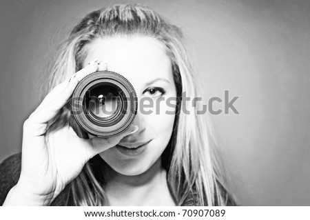 vintage portrait of beautiful young woman holding camera lens like it was spyglass. Black & White - stock photo