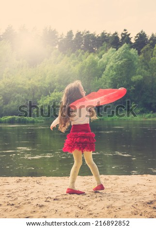 Vintage portrait of cute girl dancing with red Scarf near the river  - stock photo