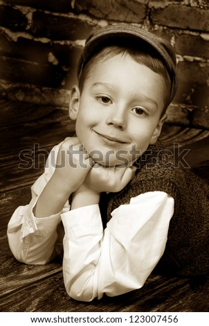 vintage portrait of elegant little boy in golfer cap and wool vest lying on wooden floor against a brick wall background - stock photo