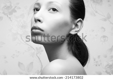 Vintage portrait of glamorous retro girl posing over vintage wall. Hollywood style (film noir). Perfect skin and hairdo. Natural make-up. Close up. Black and white (monochrome) studio shot - stock photo