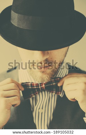 Vintage portrait of young gentleman in hat correcting his bowtie - stock photo