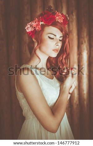 vintage portrait of young woman at the wooden background with flower ringlet - stock photo