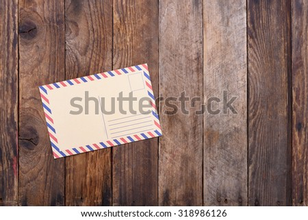 Vintage post card on old wooden table with copy space - stock photo