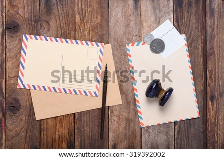 Vintage postcard and retro envelope with a stamp and old coins on wooden table