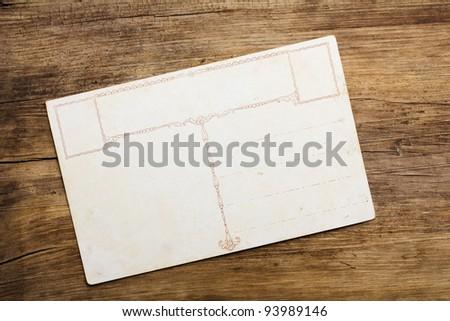 Vintage postcard on wooden table - stock photo