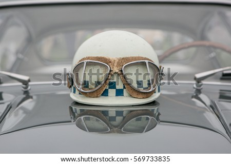 Vintage Racing Helmet And Goggles Sitting On The Hood Of A Italian Sports Car