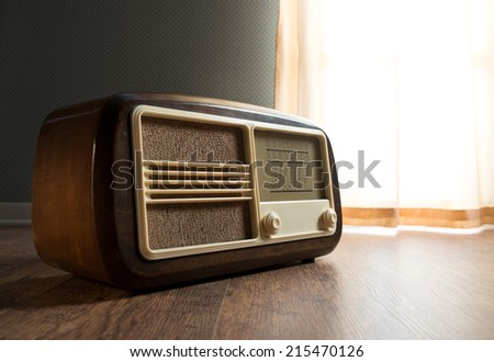 Vintage radio next to a window with curtain on hardwood floor. - stock photo