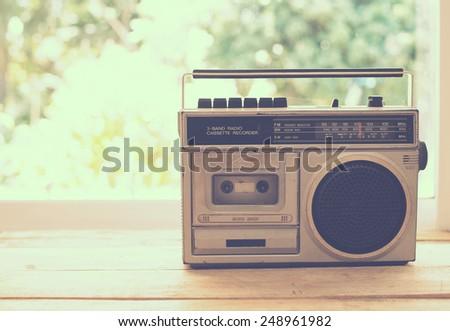 vintage radio on table nature background, instagram filter - stock photo