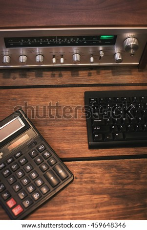 vintage receiver and calculator on a wooden background.