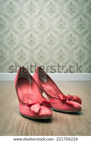 Vintage red dotted female shoes with ribbon on hardwood floor with retro wallpaper on background. - stock photo