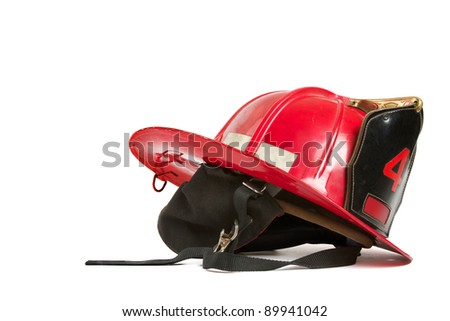 Vintage red fire fighters helmet with dark grey ear flaps, straps, black leather crest, brass trim, and gold stitching. Table top still life on white background, horizontal format with copy space. - stock photo