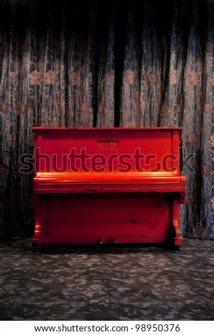 Vintage red piano in dark theater or nightclub interior over floral ornate curtains background - stock photo