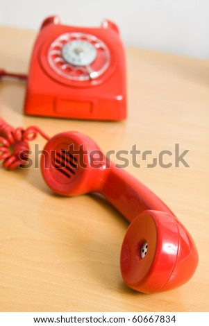 Vintage red telephone on wooden table - stock photo