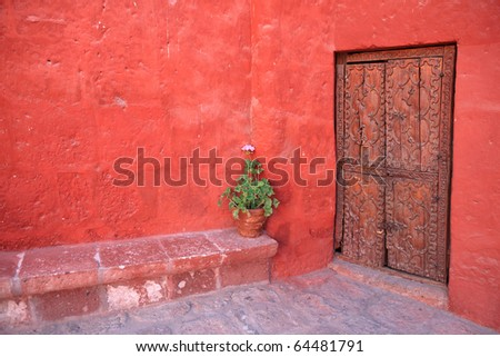Vintage red wall with old decorative wood door. - stock photo