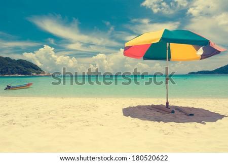 Vintage retro beach with umbrella  - stock photo