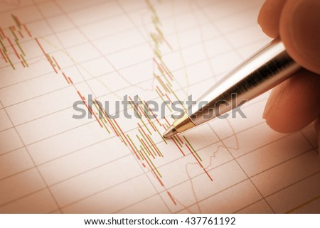 Vintage / retro color effect : Chart of financial instruments has been analysed / examined by a technical trader analyst with a blue ballpoint pen pointing on a red and green candle stick signal. - stock photo