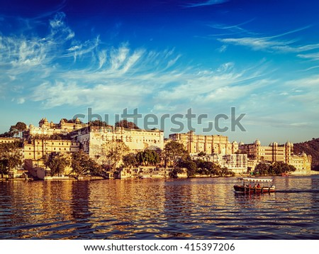 Vintage retro effect filtered hipster style image of City Palace and tourist boat on lake Pichola on sunset. Udaipur, Rajasthan, India - stock photo