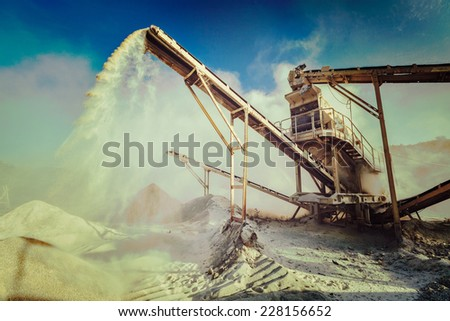 Vintage retro effect filtered hipster style image of Industrial background - crusher (rock stone crushing machine) at open pit mining and processing plant for crushed stone, sand and gravel - stock photo