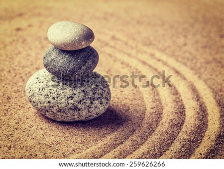 Vintage retro effect filtered hipster style image of Japanese Zen stone garden - relaxation, meditation, simplicity and balance concept  - pebbles and raked sand tranquil calm scene - stock photo