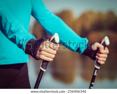 Vintage retro effect filtered hipster style image of nordic walking exercise adventure hiking concept - closeup of woman's hand holding nordic walking poles - stock photo
