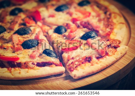 Vintage retro effect filtered hipster style image of sliced ham pizza with capsicum and olives on wooden board on table - stock photo