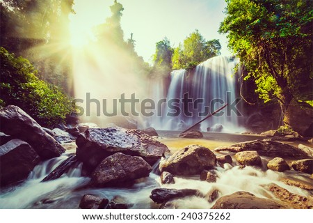 Vintage retro effect filtered hipster style image of tropical waterfall with sun rays in Cambodia - stock photo