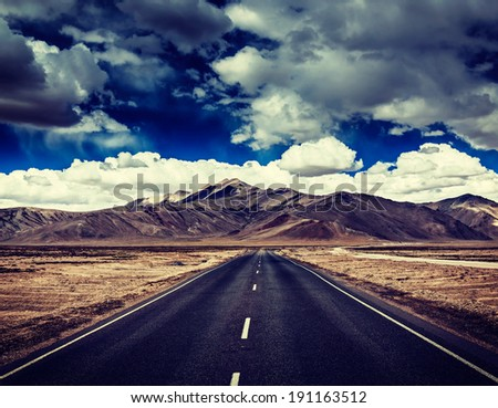 Vintage retro effect filtered hipster style travel image of Travel forward concept background - road on plains in Himalayas with mountains and dramatic clouds. Manali-Leh road, Ladakh, India - stock photo