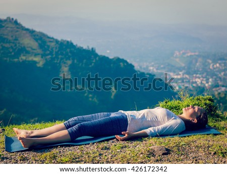 Vintage retro effect hipster style image of woman relaxes in yoga asana Savasana - corpse pose outdoors in Himalayas. Himachal Pradesh, India - stock photo