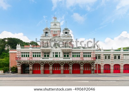 Vintage retro fire station building with red gates and brick walls