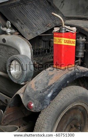 Vintage retro gas can isolated on old grunge car - stock photo