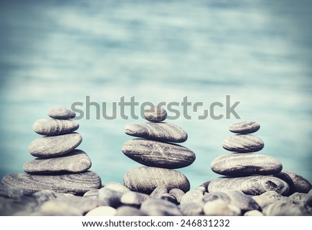 Vintage retro hipster style image of stones on beach, Zen spa concept background.