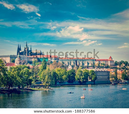 Vintage retro hipster style travel image of panorama view of Vltava river, Gradchany (Prague Castle) and St. Vitus Cathedral and Charles bridge an people in paddle boats in the Prague, Czech Republic - stock photo