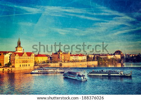 Vintage retro hipster style travel image of Vltava river with tourist boats and Prague Stare Mesto embankment view from Charles bridge on sunset with grunge texture overlaid. Prague, Czech Republic - stock photo