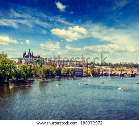 Vintage retro hipster style travel image Vltava river and Gradchany (Prague Castle), St. Vitus Cathedral, Charles bridge and people in paddle boats in Prague with grunge texture overlaid - stock photo
