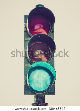 Vintage retro looking Green traffic light isolated over a white background - stock photo